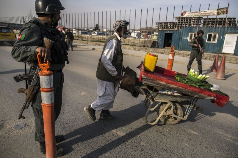 A street vendor pushes his cart past a police checkpoint in Kabul March 31, 2014. (REUTERS File Photo)