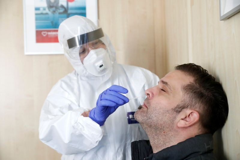 A healthcare worker collects a swab sample from a man at a COVID-19 testing site as the spread of the coronavirus disease (COVID-19) continues in Budapest, Hungary, October 27, 2020. (REUTERS Photo)