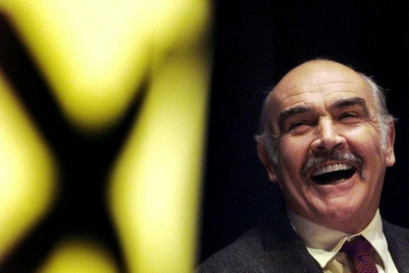 FILE PHOTO: Actor Sean Connery laughs as he listens to a speech by Alex Salmond at a Scottish National Party rally at the Edinburgh International conference centre April 26. REUTERS/Jeff J Mitchell