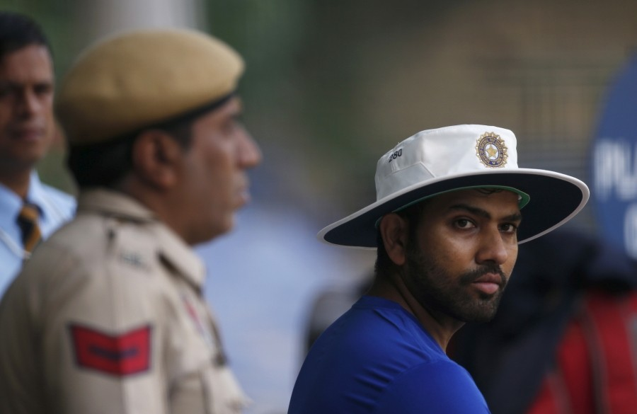 FILE PHOTO: Rohit Sharma watches his teammates practicing in the nets as a policeman stands guard during a practice session ahead of their first test cricket match against South Africa, in Mohali, India, November 4, 2015. REUTERS/Adnan Abidi