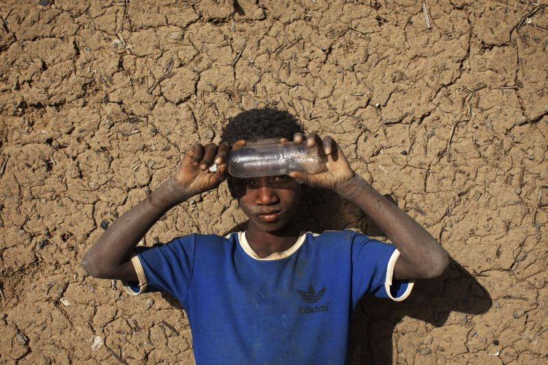 Local resident Soumaila Dicko, 9, shades his eyes from the sun with an empty plastic bottle in front of a mud brick house in Gao February 25, 2013. (REUTERS File Photo)