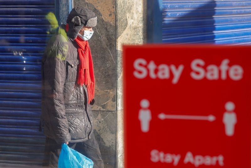 A person wearing a protective mask walks near a social distancing sign, amid the outbreak of the coronavirus disease (COVID-19), in Coventry, Britain October 25, 2020. (REUTERS Photo)