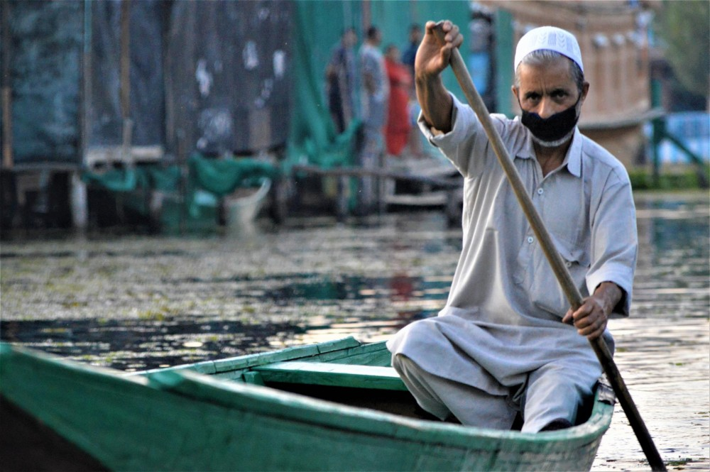 A man rows his boat on Dal Lake in Srinagar, Kashmir, India, September 12, 2020. Thomson Reuters Foundation/Athar Parvaiz