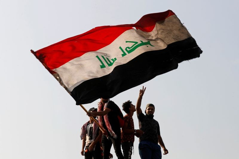 A demonstrator holds an Iraqi flag as another gestures while they gather to mark the first anniversary of the anti-government protests in Baghdad, Iraq October 25, 2020. (REUTERS Photo)