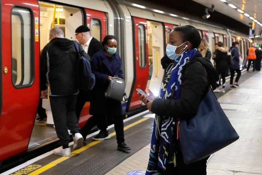 People wearing face masks to protect against the coronavirus, travel by the subway in London.  (AP Photo)