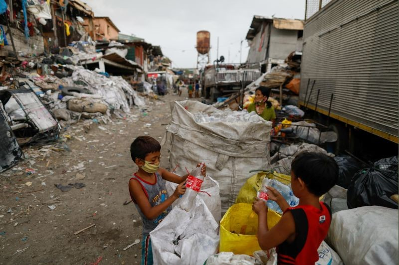 Boys wearing masks for protection against the coronavirus disease (COVID-19) remove labels from plastic bottles outside a junk shop in Tondo, Manila, Philippines, July 20, 2020. (REUTERS File Photo)