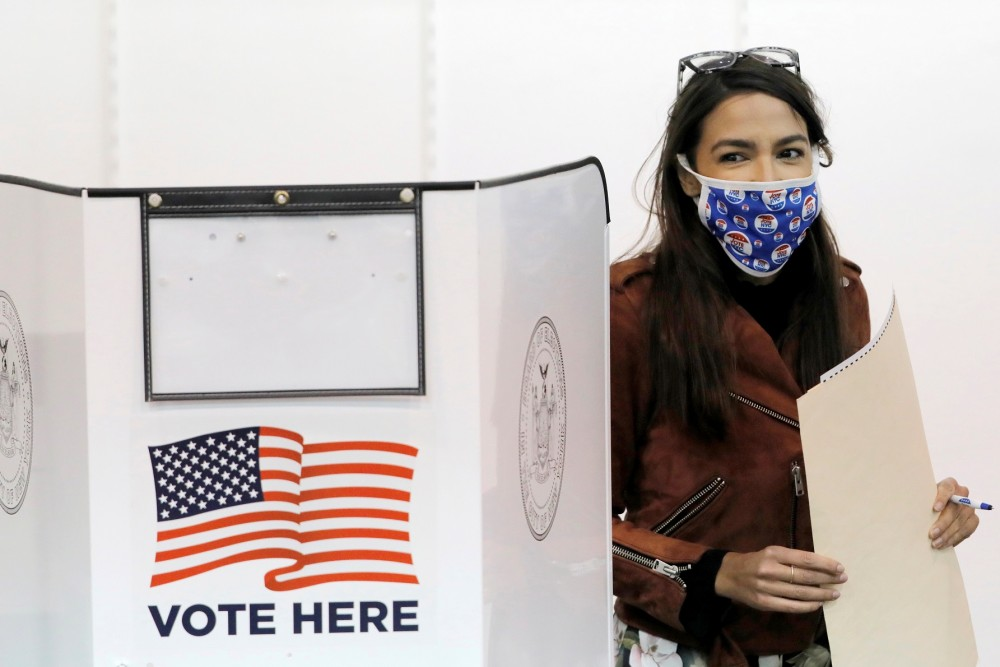 Congresswoman Alexandria Ocasio-Cortez holds her filled ballot as she votes early at a polling station in The Bronx, New York City, U.S., October 25, 2020. REUTERS/Andrew Kelly
