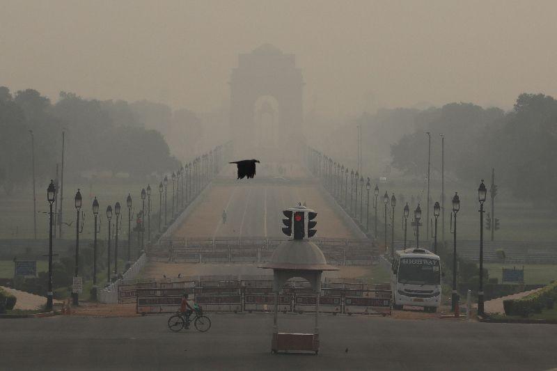 A man rides a bicycle on a hazy morning near India Gate, in New Delhi, October 14, 2020. REUTERS/Anushree Fadnavis