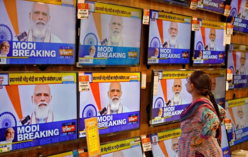 A woman wearing a protective mask watches Indian Prime Minister Narendra Modi on TV screens inside a showroom, amidst the spread of the coronavirus disease (COVID-19), in Ahmedabad, India, October 20, 2020. REUTERS/Amit Dave