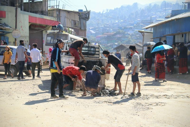 Members of The Gigglers and United Labours Society filling up a pothole with gravel and soil at High School Junction, Tuensang town on November 7. (Morung Photo)