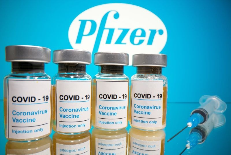 """Vials with a sticker reading, """"COVID-19 / Coronavirus vaccine / Injection only"""" and a medical syringe are seen in front of a displayed Pfizer logo in this illustration taken October 31, 2020. (REUTERS File Photo)"""