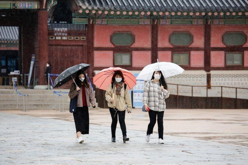 Tourists wearing masks walk with umbrellas as it rains amid the coronavirus disease (COVID-19) pandemic at Gyeongbok Palace in central Seoul, South Korea, November 19, 2020. (REUTERS File photo)