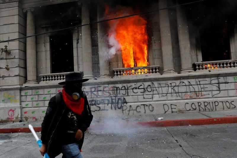 A man walks past an office of the Congress building set on fire by demonstrators during a protest demanding the resignation of President Alejandro Giammattei, in Guatemala City, Guatemala November 21, 2020. REUTERS/Luis Echeverria