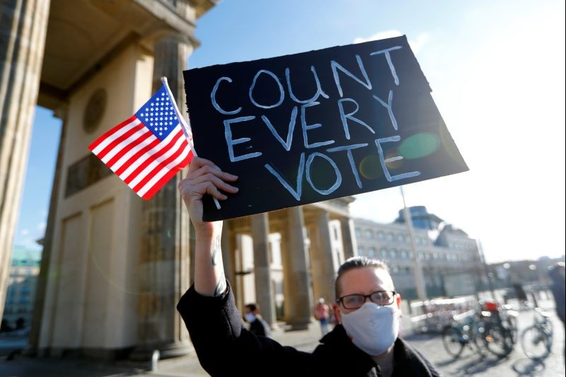 """A demonstrator holds a placard and a U.S. flag during the """"Count the Votes! Rally for Fair Elections in the USA"""" organized by Young Democrats Abroad following the 2020 U.S. presidential election, next to the Brandenburg Gate, in Berlin, Germany November 4, 2020. (REUTERS Photo)"""