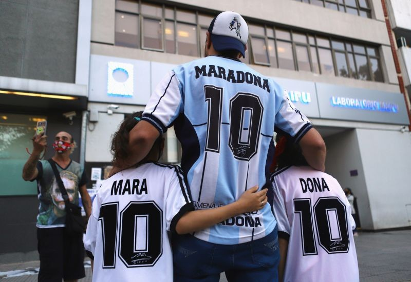 FILE PHOTO: Fans of Argentine soccer great Diego Maradona, Walter Rotundo and his twin daughters Mara and Dona, who are named after Maradona, pose for a photograph outside the clinic where Maradona underwent brain surgery, in Olivos, on the outskirts of Buenos Aires, Argentina November 5, 2020. REUTERS/Matias Baglietto