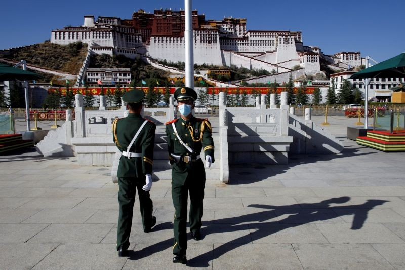 FILE PHOTO: Paramilitary police officers swap positions during a change of guard in front of Potala Palace in Lhasa, during a government-organised tour of the Tibet Autonomous Region, China, October 15, 2020. Picture taken October 15, 2020. REUTERS/Thomas Peter/File Photo