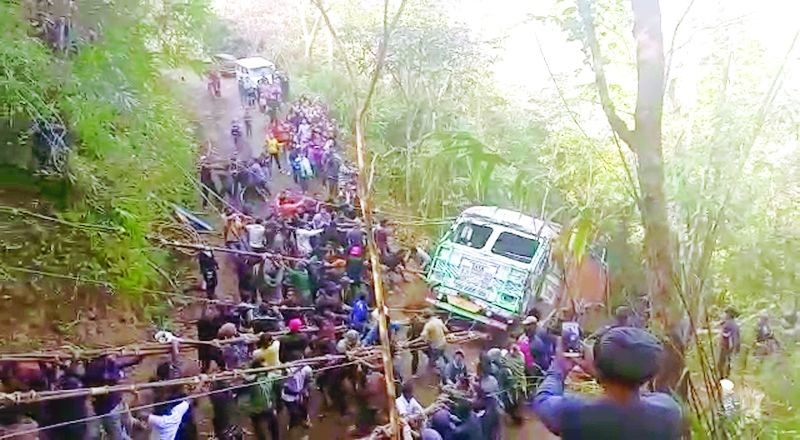 A screen-grab from a video showing the people of Kutsapo pulling up a truck which had fallen off the road.