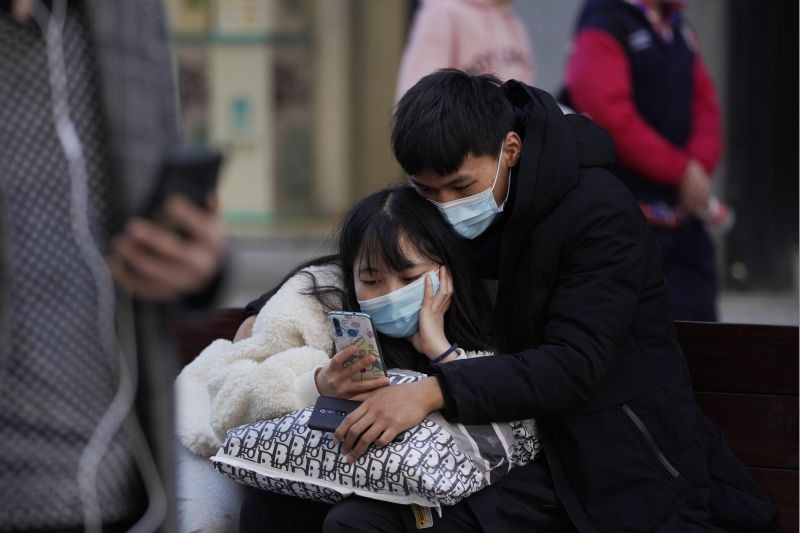 A man and woman wearing masks to help protect themselves from the coronavirus share a smartphone on the street in Wuhan in central China's Hubei province on January 14, 2021. A global team of researchers for the World Health Organization arrived Thursday in the Chinese city where the coronavirus pandemic was first detected to conduct a politically sensitive investigation into its origins amid uncertainty about whether Beijing might try to prevent embarrassing discoveries. (AP/PTI Photo)