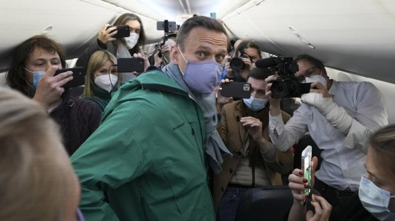Kremlin critic Alexei Navalny is surrounded by journalists inside the plane prior to his flight to Moscow in the Airport Berlin Brandenburg (BER) in Schoenefeld, near Berlin, Germany, Sunday, Jan. 17, 2021. (AP /Mstyslav Chernov)