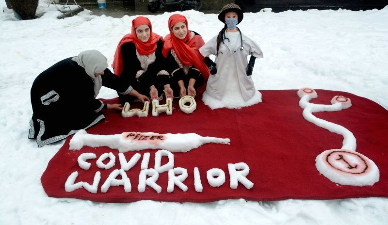 Srinagar: Two sisters Qurat-ul-Ain Zohra and Aiman Zohra along with their mother give a final touch to a snow sculpture to honour health workers and their fight against COVID-19, after a heavy snowfall, outside their residence in Srinagar, Sunday, Jan. 10, 2021. (PTI Photo)