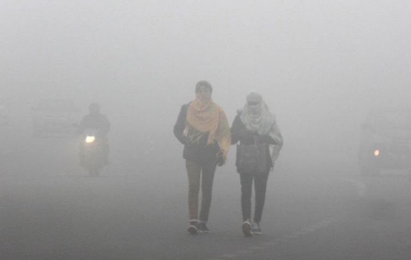 Gurugram: Commuters walk on a road amid low visibility due to fog, on a cold winter morning in Gurugram, Tuesday, Jan. 19, 2021. (PTI Photo)