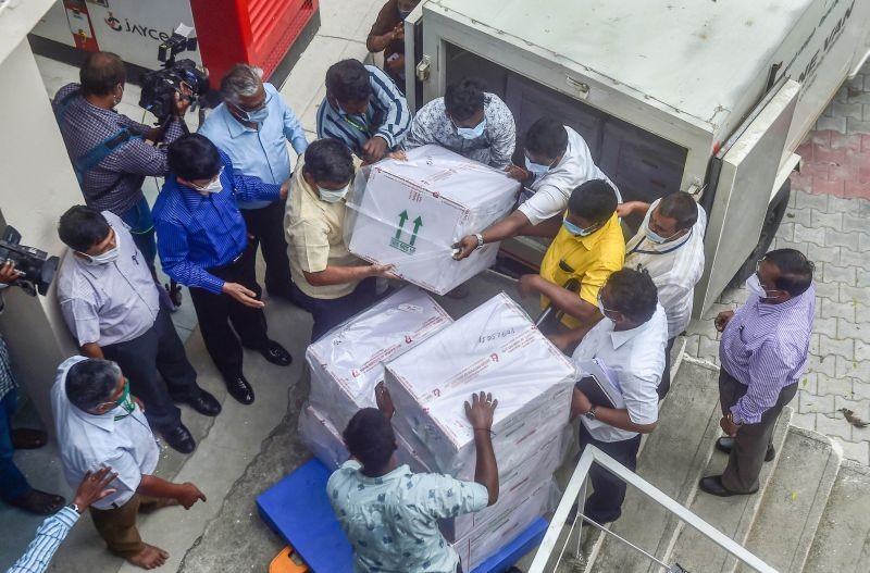 Workers unload packets containing Covishield vaccine after the first batch of  vaccines from the Serum Institute of India arrived at a storage facility in Chennai on January 12, 2021. (PTI Photo)