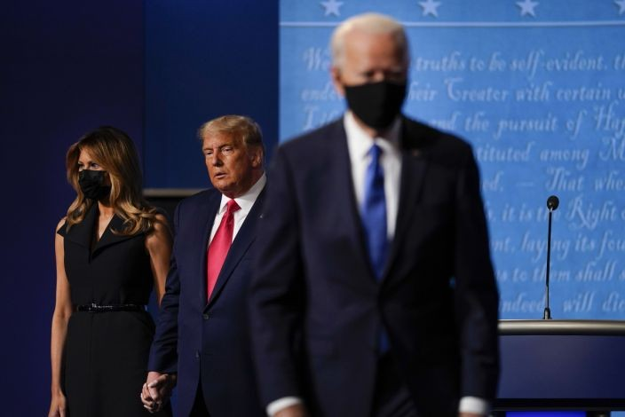 FILE - In this Oct. 22, 2020, file photo first lady Melania Trump, left, and President Donald Trump, center, remain on stage as Democratic presidential candidate former Vice President Joe Biden, right, walk away at the conclusion of the second and final presidential debate at Belmont University in Nashville, Tenn. (AP Photo/Julio Cortez, File)