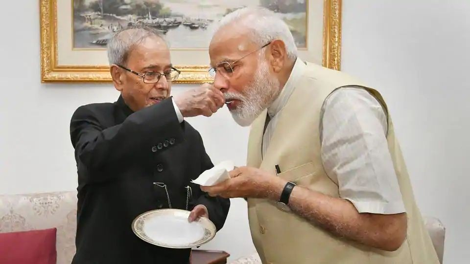 In the photographs accompanying the tweet, Pranab Mukherjee, known for his reserved, even stern demeanour was seen offering sweets to PM Modi, in the traditional Indian way of felicitation or celebration. (PTI PHOTO.)