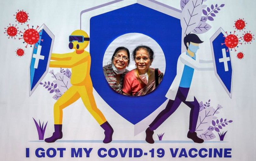 Senior citizens pose for photographs with a cut-out on being administered the COVID-19 vaccine at a paid centre at SRCC Hospital in Mumbai. Photograph: Kunal Patil/PTI Photo