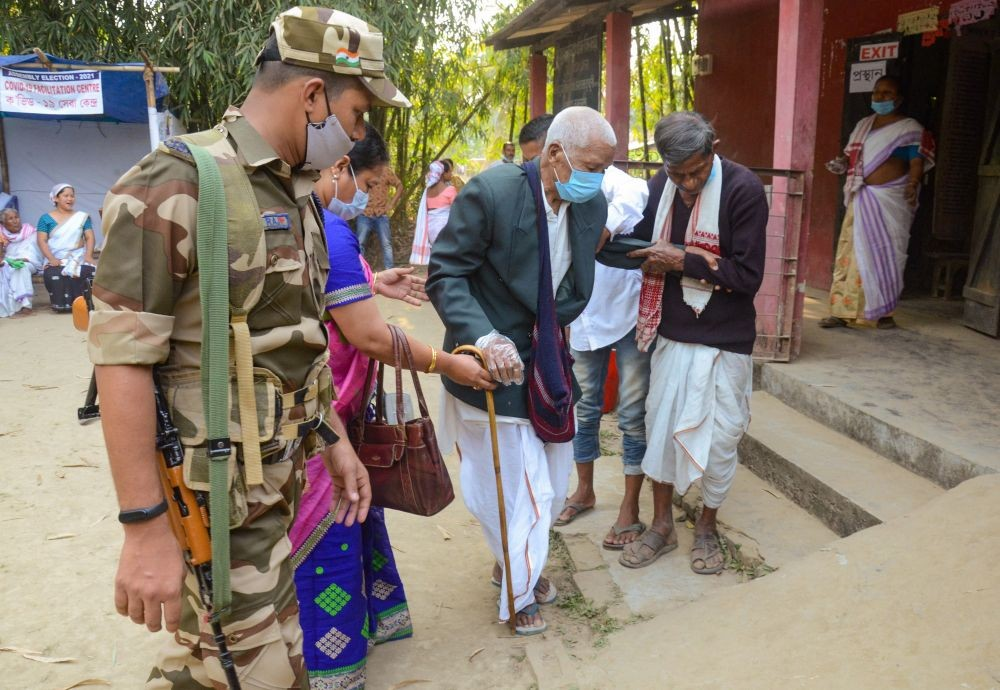 Dibrugarh: An elderly voter is helped to cast vote at a polling booth during the 1st phase of Assam Assembly elections in Lahoal constituency of Dibrugarh district, Saturday, March 27, 2021. (PTI Photo)