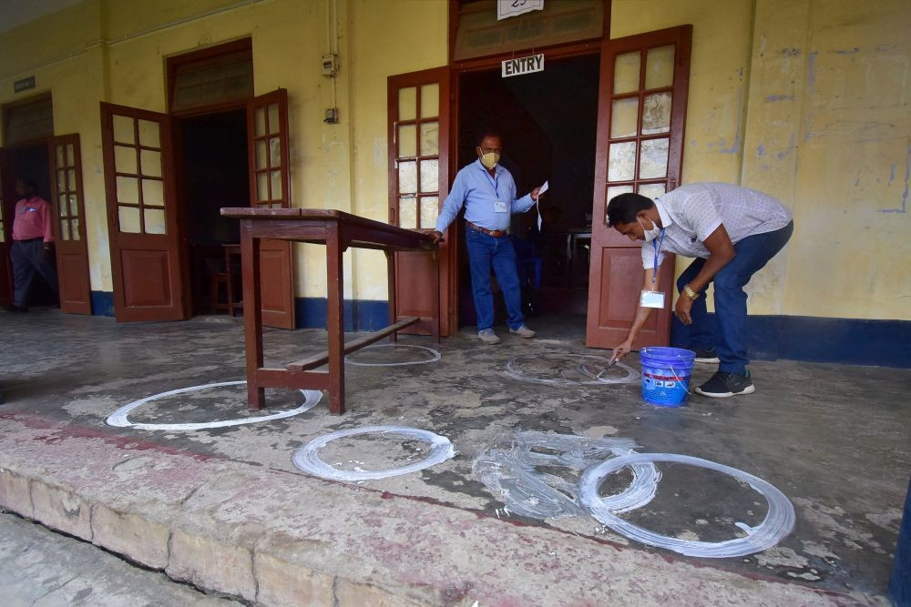 Nagaon: A polling officer draws markers on a floor to ensure social distancing as coronavirus cases spike across the country, on the eve of the second phase of Assam assembly polls, in Nagaon district, Wednesday, March 31, 2021. (PTI Photo)(
