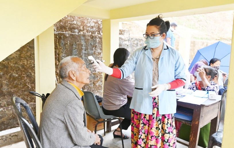 A health worker testing the temperature of a patient who came to avail the free medical services organized by Benpulin Semchir Telongjem at Government Middle School, Kumlong Ward on April 10. (Photo Courtesy: Imkongsenla)