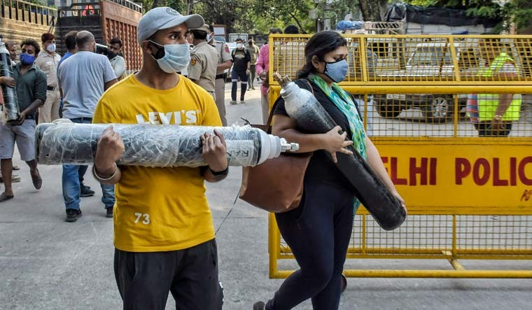 Relatives of COVID-19 patients carry oxygen cylinders themselves to tend to their relatives, at Mayapuri in New Delhi | PTI