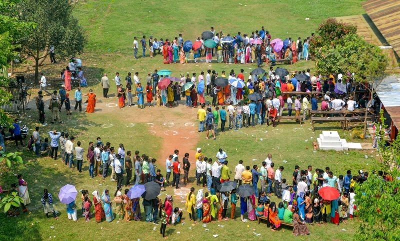 Voters queue up to cast their votes at a polling station, during the third and final phase of Assam Assembly election, in Guwahati on April 6. (PTI Photo)