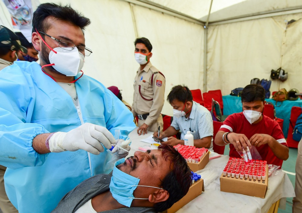 A health worker collects a nasal sample from a passenger for COVID-19 test, amid coronavirus pandemic, in New Delhi on April 2. (PTI Photo)