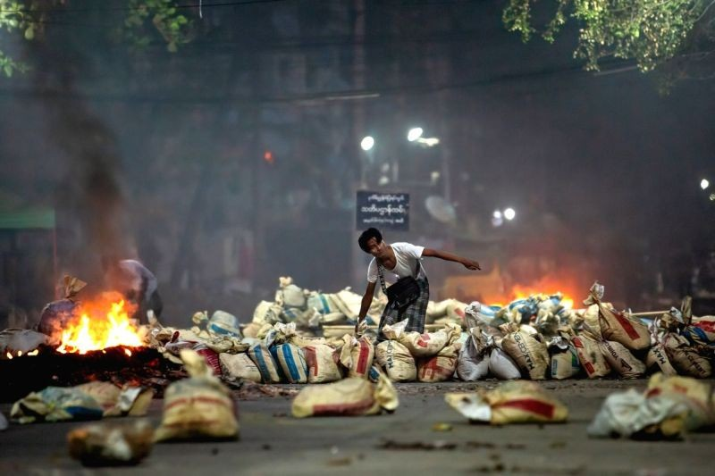 A demonstrator stacks bags on a street as a barricade during a demonstration against the military coup and the detention of civilian leaders. (IANS Photo)