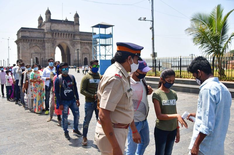 People queue up as they wait for their turn to undergo a mandatory COVID-19 test before entering the Gateway of India, in Mumbai on April 4. (PTI Photo)