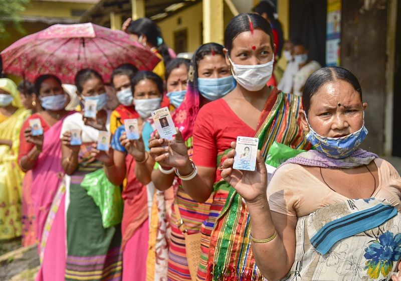 Hajong tribal women show their voter identity cards as they wait in the queue to cast their votes at a polling Station for Assembly polls, at Boko in Kamrup district on  April 6, 2021. (PTI Photo)