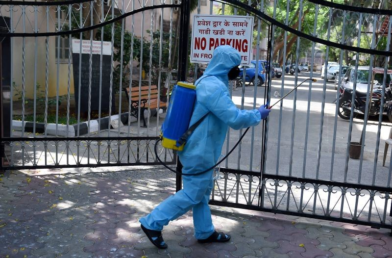 A worker sanitises an area outside a residential complex as a precautionary measure against COVID-19, in Mumbai on April 6, 2021.(PTI Photo)