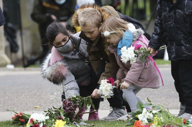 Children arrive to leave flowers at Cambridge Gate, at Windsor Castle, one day after the death of Britain's Prince Philip, in Windsor, England on April 10, 2021. Britain's Prince Philip, the irascible and tough-minded husband of Queen Elizabeth II who spent more than seven decades supporting his wife in a role that mostly defined his life, died on Friday. (AP/PTI Photo)