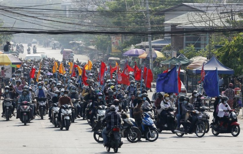 "Protesters carry flags as they drive their motorcycles during an anti-coup protest in Mandalay, Myanmar on March 25, 2021. Protesters against last month's military takeover in Myanmar returned to the streets in large numbers Thursday, a day after staging a ""silence strike"" in which people were urged to stay home and businesses to close for the day. (AP/PTI File Photo)"