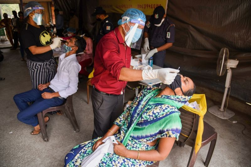 Medics from Navi Mumbai Municipal Corporation (NMMC) collect swab sample of traders and workers for COVID-19 tests, at APMC Turbhe in Navi Mumbai on April 9. (PTI Photo)