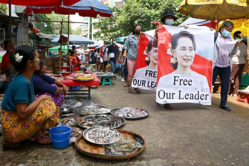 Anti-coup protesters walk through a market with images of ousted Myanmar leader Aung San Suu Kyi at Kamayut township in Yangon, Myanmar on April 8, 2021. They walked through the markets and streets of Kamayut township with slogans to show their disaffection for military coup.  (AP/PTI Photo)