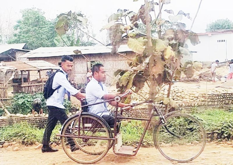 Ato(on tricycle) being helped by another student on their way to college on April 15. (Photo Courtesy: Hoto Yeptho)