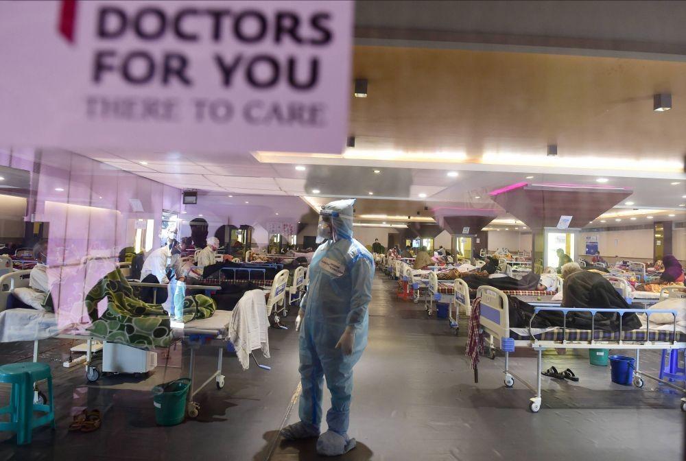 New Delhi: A health worker inspects COVID-19 patients undergoing treatment at Shehnai Banquet Hall, converted into an isolation centre amid surge in coronavirus cases, near LNJP Hospital in New Delhi, Sunday, April 18, 2021. (PTI Photo/Kamal Kishore)