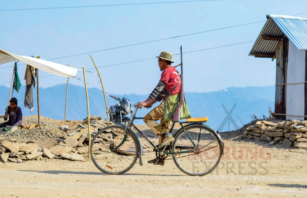 A hunter cycles past a quarry in Kuthur village in the Tuensang district. (Morung Photo by Moses Hongang Chang)
