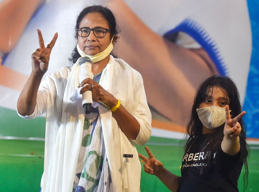 Kolkata: TMC supremo and West Bengal Chief Minister Mamata Banerjee flashes the victory sign with her nephew Abhisekh Banerjee's daughter Azania (R), during interaction with media after trends show her party's wins in the State Assembly Election 2021, in Kolkata, Sunday, May 2, 2021. (PTI Photo/Swapan Mahapatra)