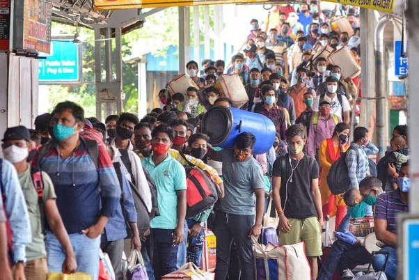 Migrants stand in a queue outside Hatia railway station to board outstation trains, amid the rise in Covid-19 cases across the country, in Ranchi. PTI Photo
