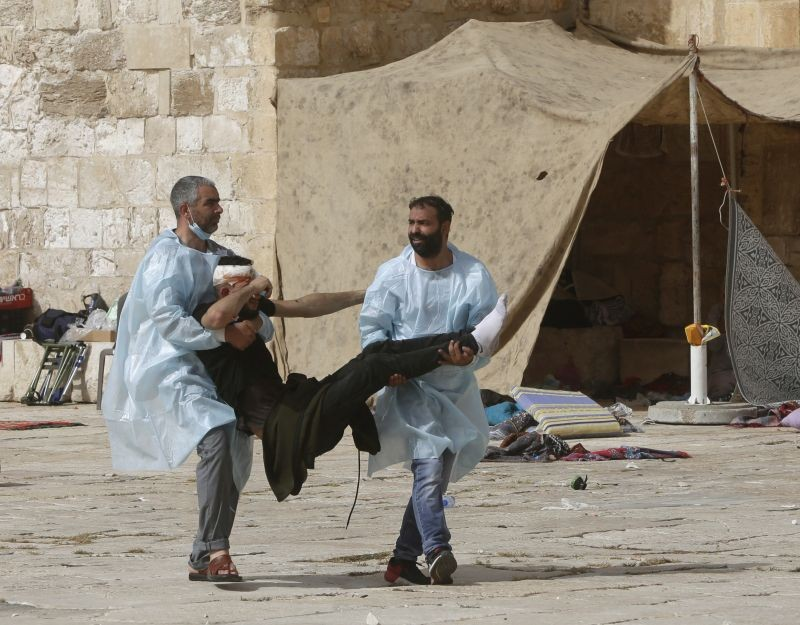 Palestinians evacuate a wounded man during clashes with Israeli security forces at the Al-Aqsa Mosque compound in Jerusalem's Old City on May 10, 2021. Israeli police clashed with Palestinian protesters at the flashpoint Jerusalem holy site on Monday, the latest in a series of confrontations that is pushing the contested city to the brink of eruption. Palestinian medics said at least 180 Palestinians were hurt in the violence at the Al-Aqsa Mosque compound, including 80 who were hospitalized. (AP/PTI Photo)