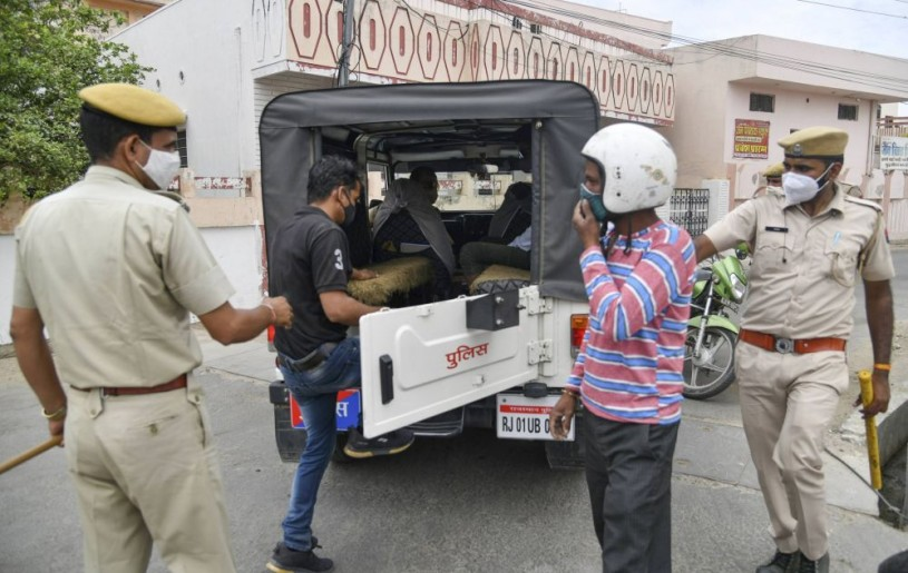 Ajmer: A police personnel nabs an offender amid a curfew in Ajmer, Rajasthan, Tuesday, May 4, 2021. (PTI Photo)